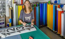 Frau arbeitet mit Folien in der Werbetechnik