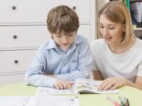 Lehrerin hilft Jungen beim Lesen