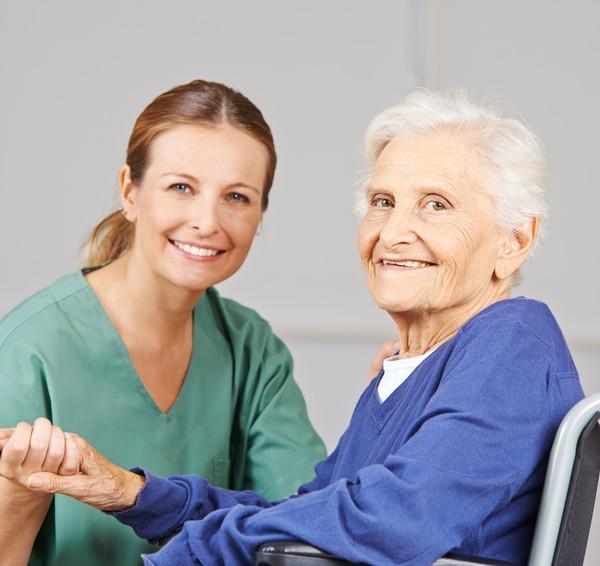 Altenpflege durch lächelnde Krankenschwester bei einer glücklichen Seniorin