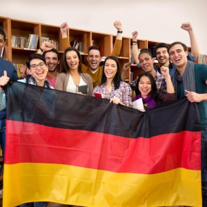 Excited students with hands raised and smiling faces present Germany country with German flag