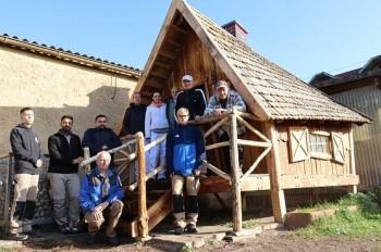 MItarbeiter des VHS-BILDUNGSWERK Nordhausen posieren stolz vor ihrem selbst gebauten Hexenhaus.