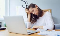 Frau sitzt müde vor dem Laptop